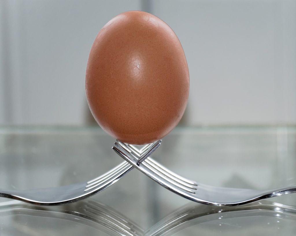 Ein Ei aufrecht auf zwei verschränkten Gabeln stehend